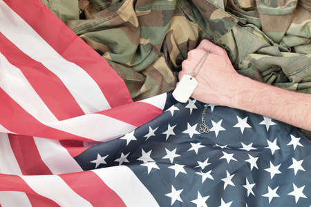 Male hand holds dog tag on USA flag and military uniform background. Concept of joining the US military Imagens