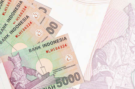 5000 Indonesian rupiah bills lies in stack on background of big semi-transparent banknote. Abstract business background with copy space