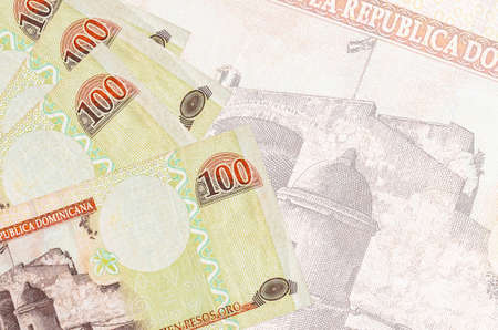 100 Dominican peso bills lies in stack on background of big semi-transparent banknote. Abstract business background with copy space 免版税图像