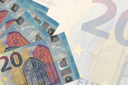 20 euro bills lies in stack on background of big semi-transparent banknote. Abstract business background with copy space