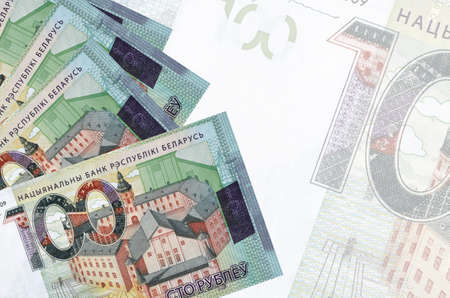 100 Belorussian rubles bills lies in stack on background of big semi-transparent banknote. Abstract business background with copy space 免版税图像
