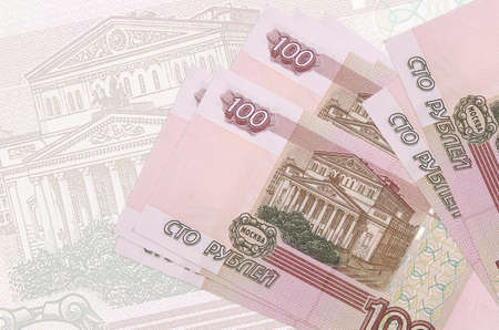 100 russian rubles bills lies in stack on background of big semi-transparent banknote. Abstract presentation of national currency. Business concept