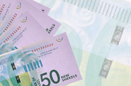 50 Israeli new shekels bills lies in stack on background of big semi-transparent banknote. Abstract business background with copy space