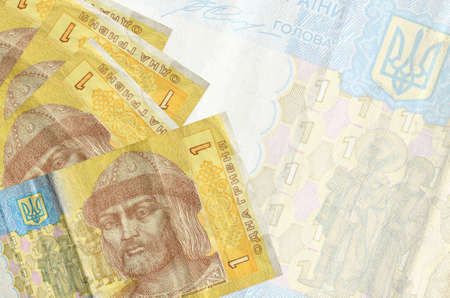 1 Ukrainian hryvnia bills lies in stack on background of big semi-transparent banknote. Abstract business background with copy space 免版税图像