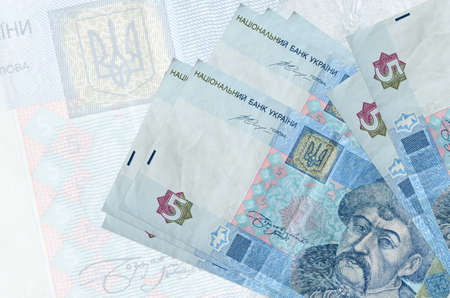5 Ukrainian hryvnias bills lies in stack on background of big semi-transparent banknote. Abstract presentation of national currency. Business concept