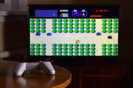 KHARKOV, UKRAINE - NOVEMBER 12, 2020: Dendy video game controller on table with The Legend of Zelda game on big display