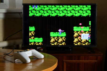 KHARKOV, UKRAINE - NOVEMBER 12, 2020: Dendy video game controller on table with Contra game on big display 新聞圖片