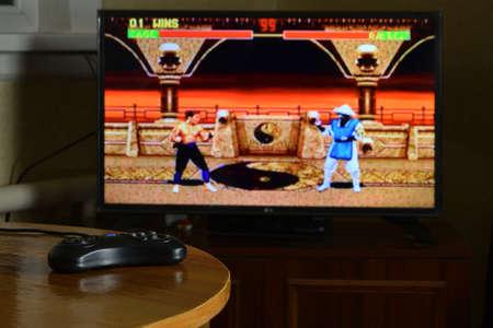 KHARKOV, UKRAINE - NOVEMBER 12, 2020: Sega mega drive video game controller on table with Mortal Kombat 2 game on big display