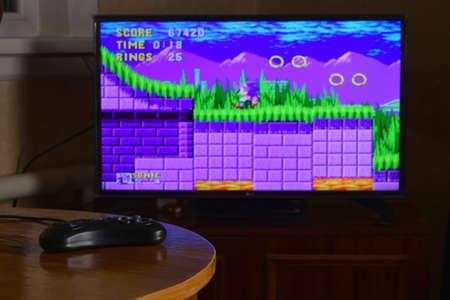 KHARKOV, UKRAINE - NOVEMBER 12, 2020: Sega mega drive video game controller on table with Sonic the Hedgehog game on big display
