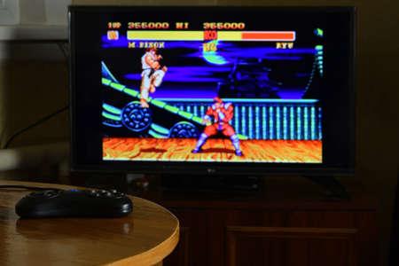 KHARKOV, UKRAINE - NOVEMBER 12, 2020: Sega mega drive video game controller on table with Street Fighter 2 game on big display