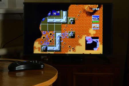 KHARKOV, UKRAINE - NOVEMBER 12, 2020: Sega mega drive video game controller on table with Dune 2 Battle for Arrakis game on big display