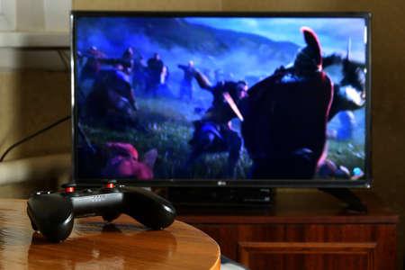 KHARKOV, UKRAINE - NOVEMBER 12, 2020: Video game controller Gamesir g3s on table with Assassins Creed Valhalla game on big display