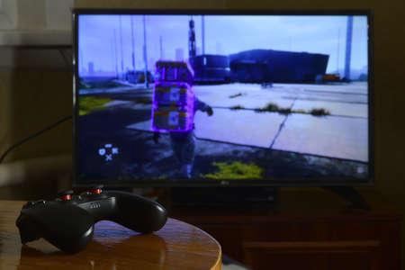 KHARKOV, UKRAINE - NOVEMBER 12, 2020: Video game controller Gamesir g3s on table with Death Stranding game on big display