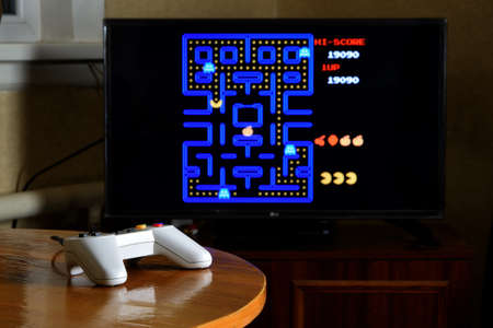 KHARKOV, UKRAINE - NOVEMBER 12, 2020: Dendy video game controller on table with Pac Man game on big display