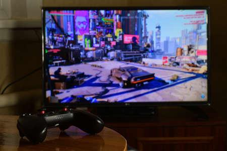 KHARKOV, UKRAINE - NOVEMBER 12, 2020: Video game controller Gamesir g3s on table with Cyberpunk 2077 game on big display