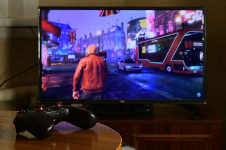 KHARKOV, UKRAINE - NOVEMBER 12, 2020: Video game controller Gamesir g3s on table with Watch Dogs Legion game on big display