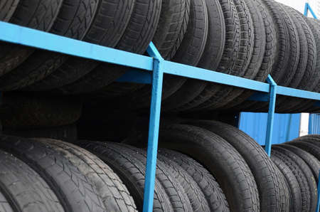 Rack with variety of car tires in automobile store. Many black tires. Tire stack background. Selective focus
