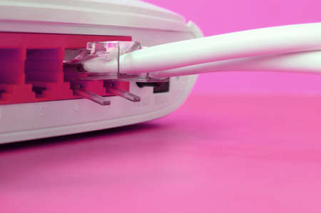 The Internet cable plugs are connected to the Internet router, which lies on a bright pink background. Items required for Internet connection