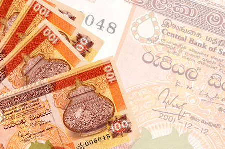 100 Sri Lankan rupees bills lies in stack on background of big semi-transparent banknote. Abstract business background with copy space