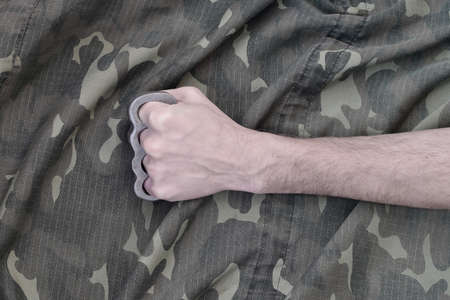 Male fist with brass knuckles on the background of a camouflage jacket. The concept of skinhead culture, homemade melee weapons