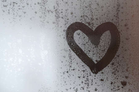 The heart is painted on the misted glass in the winter Stock Photo