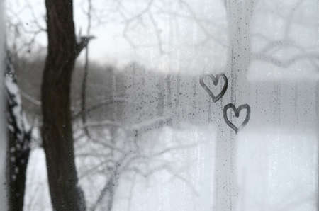 Two hearts painted on a misted glass in the winter Stockfoto