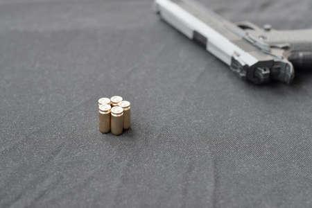 9mm bullets and pistol lie on a black fabric. A set shooting range items or a self-defense kit. Golden shells near handgun