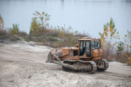 Quarry aggregate with heavy duty machinery on Construction industry. Caterpillar loader Excavator with backhoe driving to construction site quarry