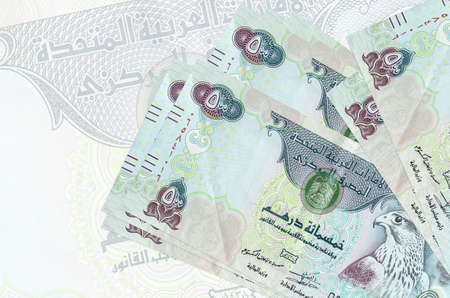 500 UAE dirhams bills lies in stack on background of big semi-transparent banknote. Abstract presentation of national currency. Business concept