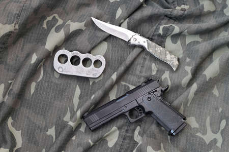 Handgun lies with brass knuckles and knife on camouflage military uniform close up. Concept of looting and illegal arms trade Banque d'images