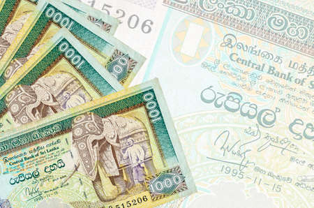 1000 Sri Lankan rupees bills lies in stack on background of big semi-transparent banknote. Abstract business background with copy space