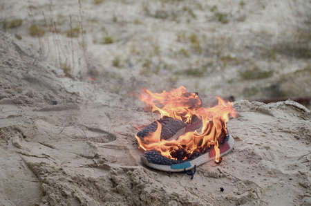 Burning sports sneakers or gym shoes on fire stand on sandy beach coast close up. Athlete burned out. Physical exertion during training concept
