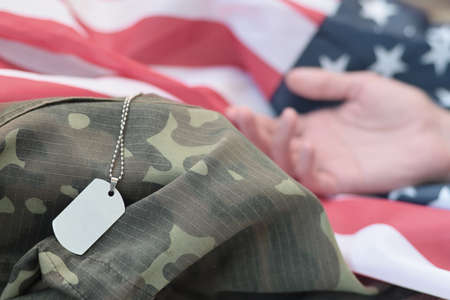 Silvery military beads with dog tag and hand of dead soldier on United States fabric flag and camouflage uniform. Killed in action unit. Memorial day concept