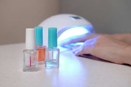 Three colorless transparent nail polish bottles in background of female hands in gel uv led nail white lamp for drying manicure. Beauty care women procedures in salon or home on gray background