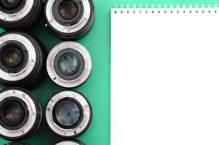 Several photographic lenses and white notebook lie on a bright turquoise background. Space for text