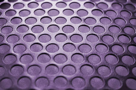 Black metal computer case panel mesh with holes on purple background. Abstract close up image