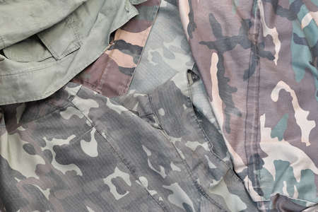 Camouflage background texture as backdrop for military service design projects. Back side of conscripts camouflage jacket with many pleats on crumpled fabric