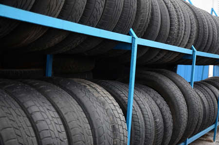 Rack with variety of car tires in automobile store. Many black tires. Tire stack background. Selective focus Foto de archivo