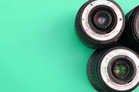 Several photographic lenses lie on a bright turquoise background. Space for text