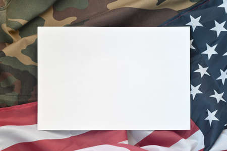 Blank paper lies on United States of America flag and folded military uniform jacket. Military symbols conceptual background banner and space for text Foto de archivo