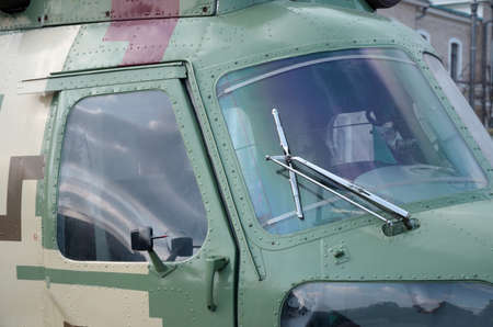 Close up view on helicopter cabin fragment. Camouflage aircraft fuselage and bulletproof glass