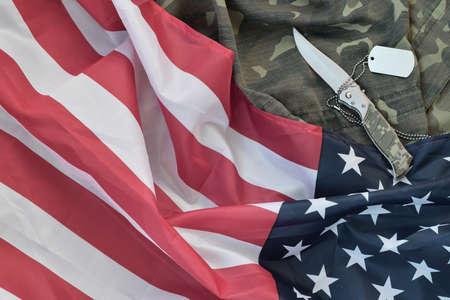 Army dog tag token and knife lies on Old Camouflage uniform and folded United States Flag. Background for Veterans day design Foto de archivo