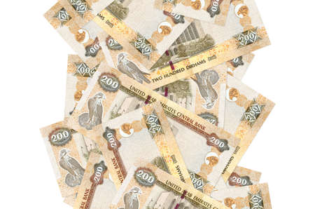 200 UAE dirhams bills flying down isolated on white. Many banknotes falling with white copy space on left and right side
