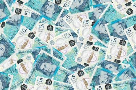 5 British pounds bills lies in big pile. Rich life conceptual background. Big amount of money