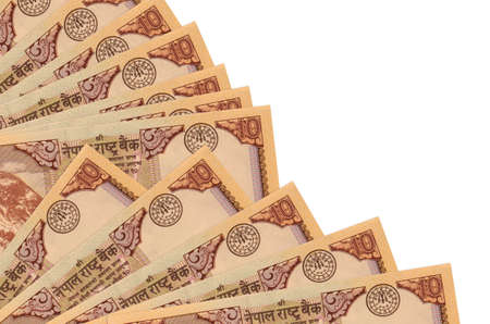 10 Nepalese rupees bills lies isolated on white background with copy space stacked in fan close up. Payday time concept or financial operations