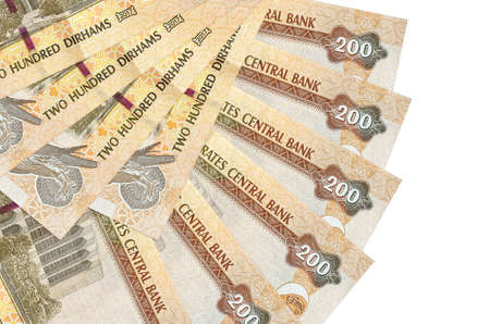 200 UAE dirhams bills lies isolated on white background with copy space stacked in fan shape close up. Financial transactions concept