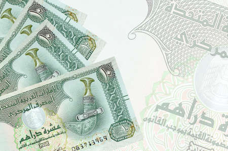 10 UAE dirhams bills lies in stack on background of big semi-transparent banknote. Abstract business background with copy space