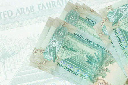 10 UAE dirhams bills lies in stack on background of big semi-transparent banknote. Abstract presentation of national currency. Business concept Stock fotó