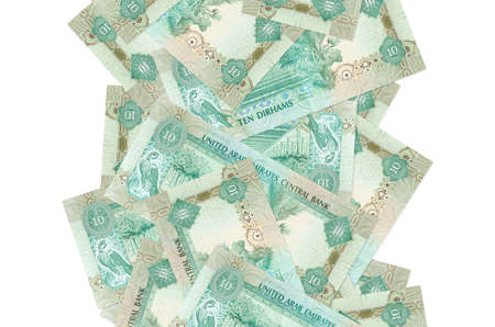 10 UAE dirhams bills flying down isolated on white. Many banknotes falling with white copy space on left and right side