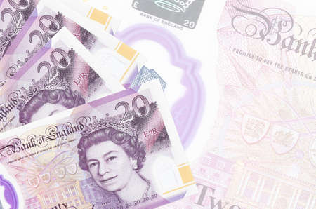 20 British pounds bills lies in stack on background of big semi-transparent banknote. Abstract business background with copy space 版權商用圖片